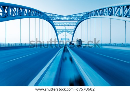 road through the bridge with blue sky background of a city. #69570682