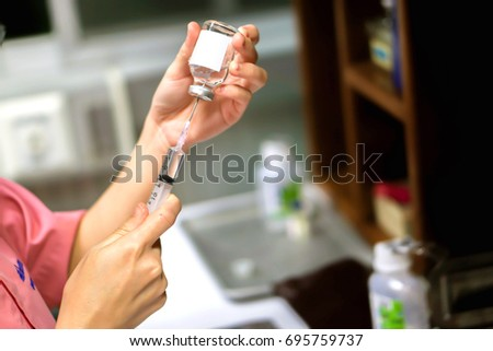 A picture of nurse hands holding a plastic syringe and vial for preparation an injection vaccine for the patient. #695759737