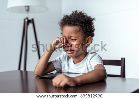little african-american boy crying while sitting with digital tablet #695812990