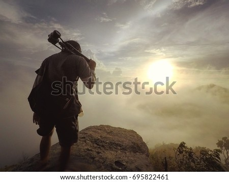 Man standing on a rock with beautiful sunset view in background. #695822461