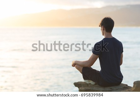 Young man meditating on top ocean cliff during sunset.  Royalty-Free Stock Photo #695839984