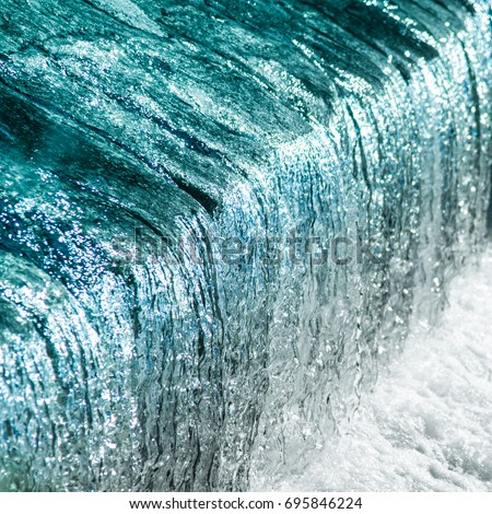 Beautiful detailed texture of flowing water in gorgeous aqua shades: From glossy watercolor baby blue, pale turquoise and sky teals to bright shallow sea and silver white colors of waterfall cascade #695846224