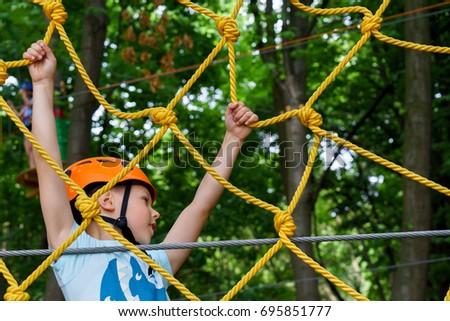 The boy climbs the rope park #695851777