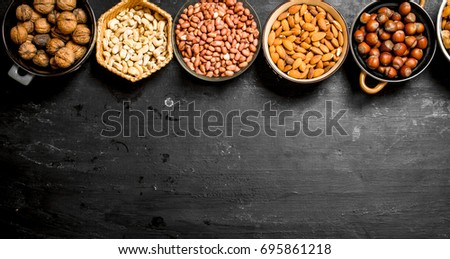 Various nuts in bowls. On a black chalkboard. #695861218