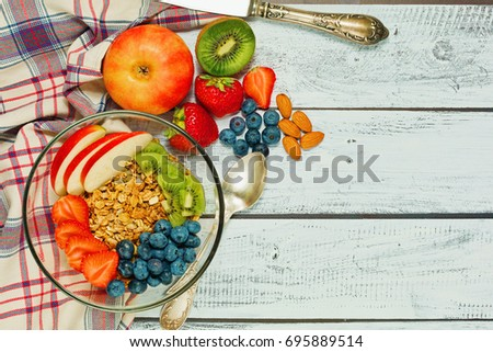 Healthy breakfast concept - multigrain granola with apple, kiwi, almonds, strawberry and blueberry - top view in rural style on wooden table with vintage knife and checkered textile #695889514