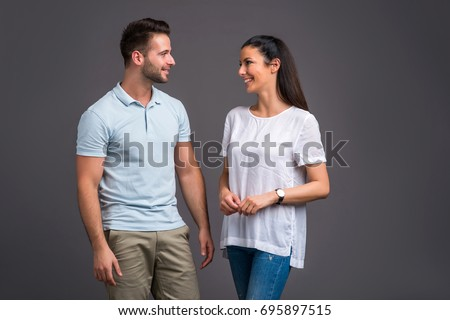 A beautiful young couple standing and laughing in good mood #695897515