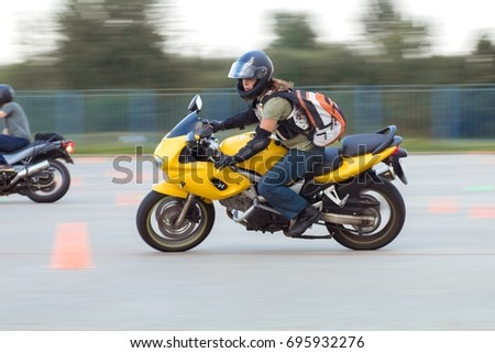 MINSK, REPUBLIC OF BELARUS - AUGUST 08, 2017: MotoGymkhana-Minsk motorcycle driving competition. Leaders around cones and artificial obstacles. Texture speed-effect with blur background. #695932276