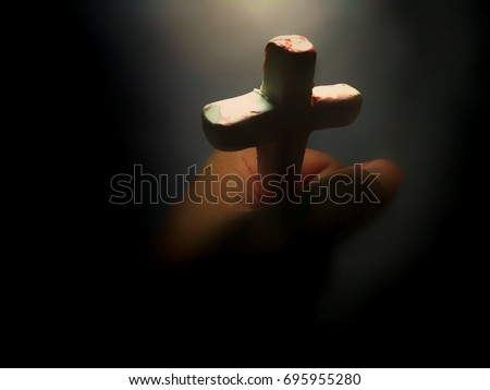 Close up Cross of Christ in blurred light hand, concept picture with shade decoration process