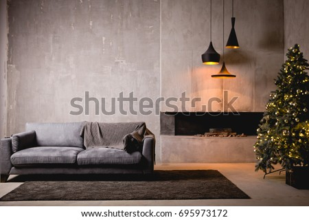 The gray velor sofa in the dark loft room has a bright light from the eternal light and an artificial fireplace. Inner attic with concrete walls and a decorated Christmas tree with gift boxes #695973172