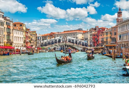Bridge Rialto on Grand canal famous landmark panoramic view Venice Italy with blue sky white cloud and gondola boat water. #696042793