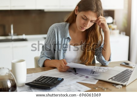 Indoor shot of casually dressed young woman holding papers in her hands, calculating family budget, trying to save some money to buy new bicycle to her son, having stressed and concentrated look Royalty-Free Stock Photo #696061069