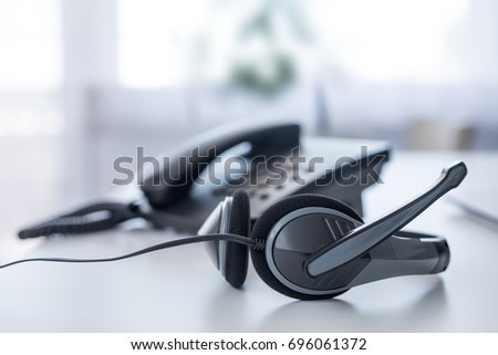 Communication support, call center and customer service help desk. VOIP headset on laptop computer keyboard. Royalty-Free Stock Photo #696061372