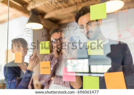 Business people meeting at office and use post it notes to share idea. Brainstorming concept. Sticky note on glass wall. Royalty-Free Stock Photo #696061477