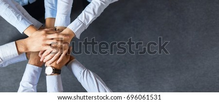 Close up top view of young business people putting their hands together. Stack of hands. Unity and teamwork concept. Royalty-Free Stock Photo #696061531
