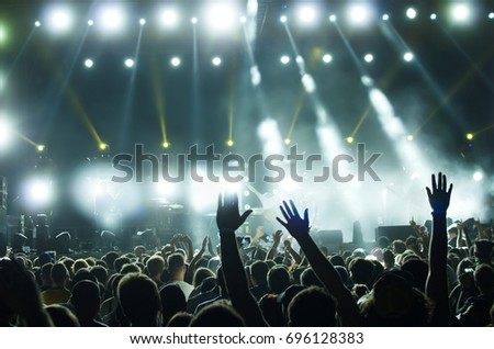 silhouettes of people at a concert in front of the scene in bright light. #696128383