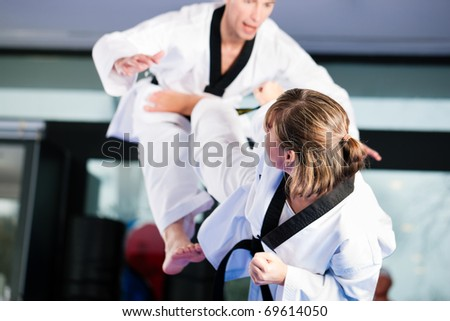 People in a gym in martial arts training exercising Taekwondo, both have a black belt #69614050