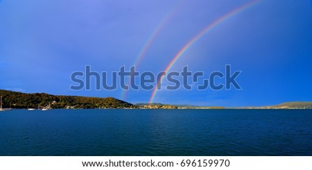 Spectacular colourful vivid rare Double Rainbow in blue sky with a tree studed horison over water.Photographed at Lake Macquarie, Central Coast New South Wales, Australia.