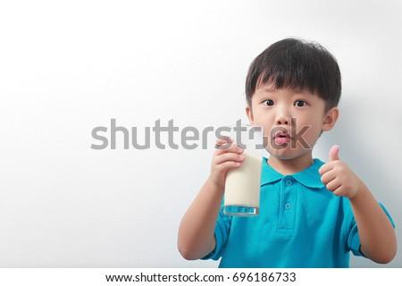 Adorable Asian boy drinking milk with milk moustache #696186733