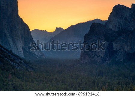 Classic Tunnel View of scenic Yosemite Valley with famous El Capitan and Half Dome rock climbing summits in beautiful golden morning light at sunrise in summer, Yosemite National Park, California, USA #696191416