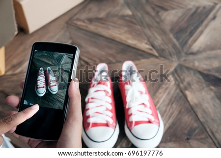 Online seller use mobile phone take a photo of product for upload to website online shop.
