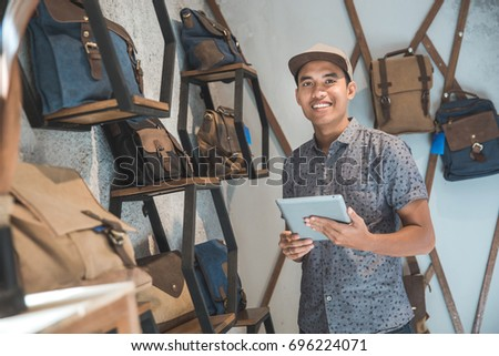 portrait of asian male business owner standing in front of his bag store with tablet #696224071