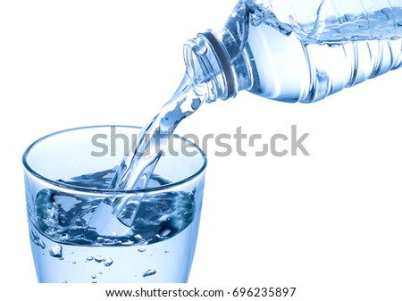 Pouring water on a glass isolated on white background. Clipping path #696235897