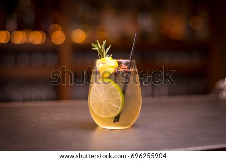 Low angle close up of ice cold modern gourmet craft cocktail of gin and tonic soda garnished by lemon slice and rosemary sprig sprinkled by juniper berries on bar with blurry restaurant bar background #696255904