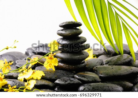 Stacked wet stones and yellow orchid with palm leaf  #696329971