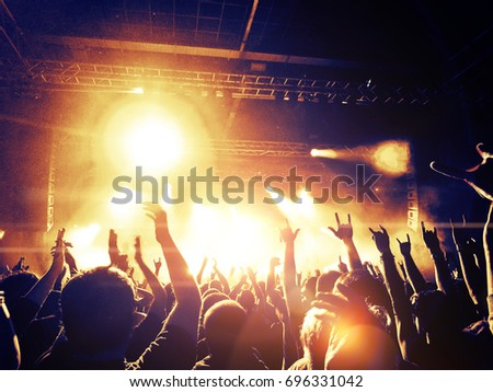 Concert crowd attending a concert, people silhouettes are visible, backlit by stage lights. Raised hands and smart phones are visible here and there. #696331042