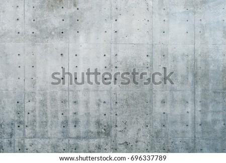 Smooth bare concrete wall with many concrete form dimples and grid lines. #696337789