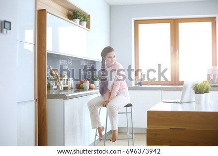 Young woman sitting on table in the kitchen. #696373942
