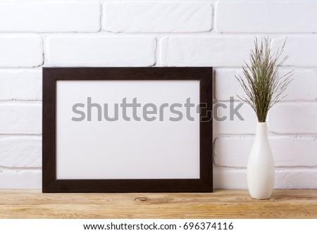 Black brown  landscape frame mockup with dark meadow grass in elegant vase near painted brick wall. Empty frame mock up for presentation design. Template framing for modern art.