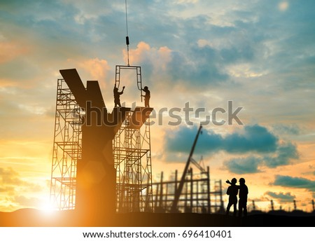 Silhouette engineer  look team construction safely to work load scaffolding over blurred background sunset pastel for industry background with Light fair Royalty-Free Stock Photo #696410401