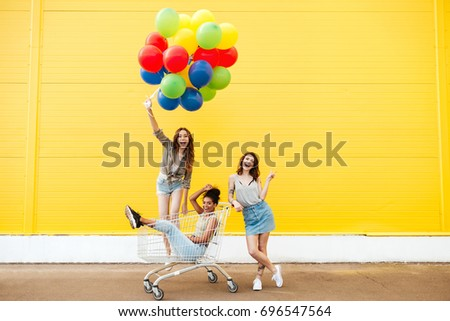 Image of young smiling women friends over yellow wall. Have fun with shopping trolley and balloons. #696547564