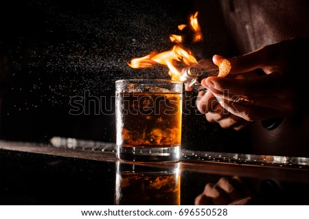 The bartender makes flame over a cocktail with orange peel close up #696550528