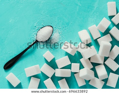 background of sugar cubes and sugar in spoon. White sugar on turquoise background. Sugar with copy space. Top view or flat lay #696633892