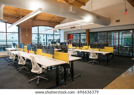 Trendy modern open concept loft office space with big windows, natural light and a layout to encourage collaboration, creativity and innovation #696636379