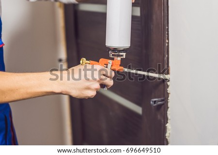 Young handyman installing door with an mounting foam in a room. #696649510