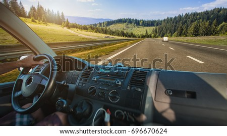 Car dashboard and steering wheel inside of car. Travel in the mountains #696670624