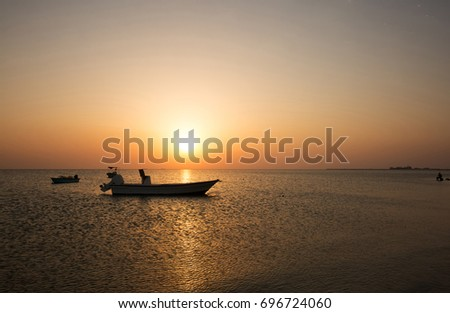 Speed boat anchored at sea shore of Busaiteen, Bahrain during sunset #696724060