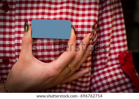 The girl's hand holds blank the badge on the shirt.Copy space. #696762754