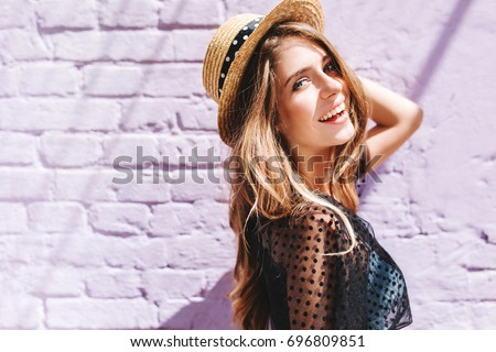 Graceful young woman with long shiny hair gladly posing while walk outside in good mood. Outdoor close-up photo of pleased girl in trendy summer hat with black ribbon enjoying sunshine.
