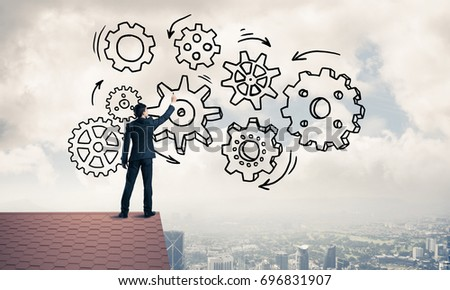 Young businessman standing on house roof and drawing gear mechanism. Mixed media #696831907