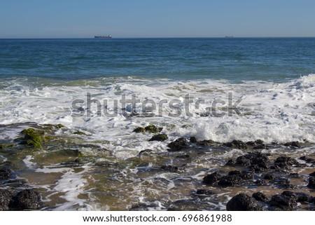 Tide ebbing out at Ocean Beach Bunbury, Western Australia on a fine morning in late winter leaves white foam amongst the  lichen covered dark basalt rocks. #696861988