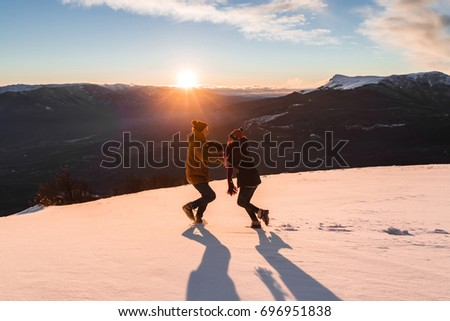 Young couple enjoying together. Having fun in snow at sunset in mountains #696951838