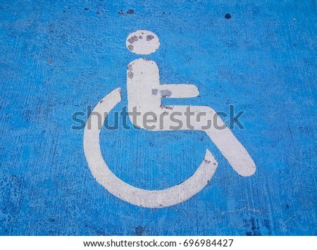 Old sign of handicapped parking with blue and white color on street. Signal is cracked color because it made for long time. #696984427