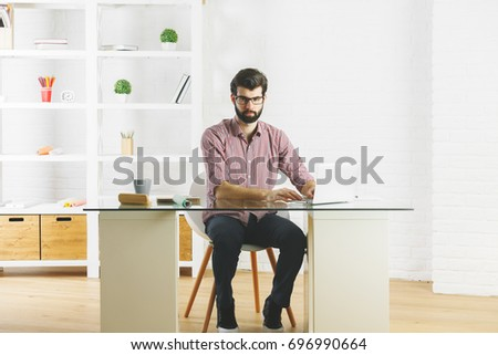Thoughtful young man using laptop computer in modern office with various items on shelf. Lifestyle concept  #696990664