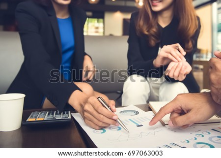 Financial adviser working with clients analyzing data at the table in cafe #697063003