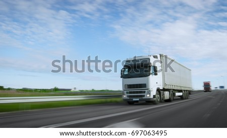 Speeding White Semi Truck with Cargo Trailer Drives on the Highway. Truck is First in the Column of Heavy Vehicles, Sun is Shining. Blur motion. #697063495
