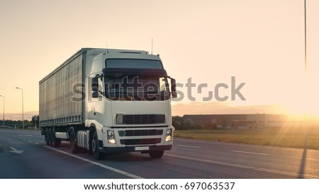 Front-View of Semi-Truck with Cargo Trailer Driving on a Highway. He's Speeding Through Industrial Warehouse Area with Sunset in the Background. #697063537
